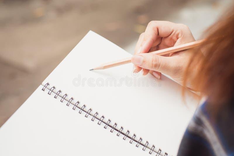 Ciérrese para arriba de las manos del ` s de la mujer que escriben en la libreta espiral colocada en la mesa de madera con los di imagen de archivo libre de regalías