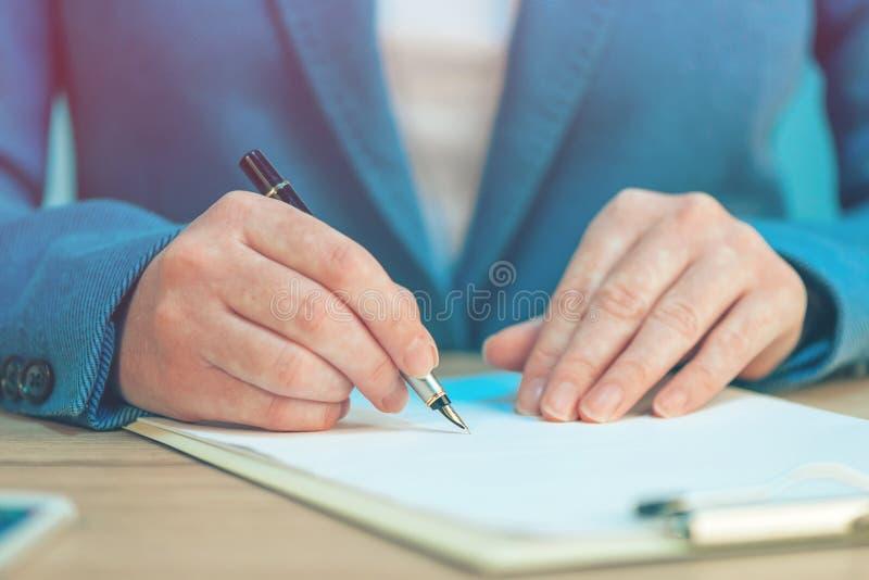 Ciérrese para arriba de las manos femeninas que escriben la firma en el acuerdo del negocio fotos de archivo libres de regalías