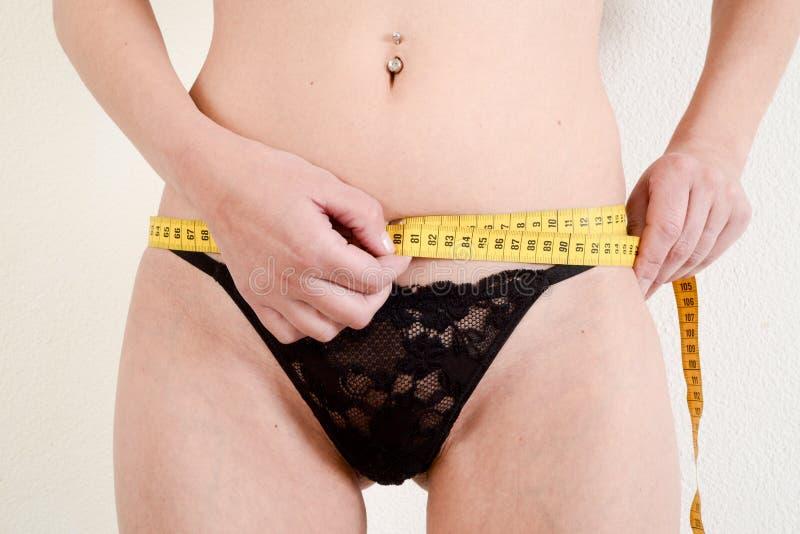 Ciérrese para arriba de las manos femeninas que miden la cintura imagen de archivo libre de regalías
