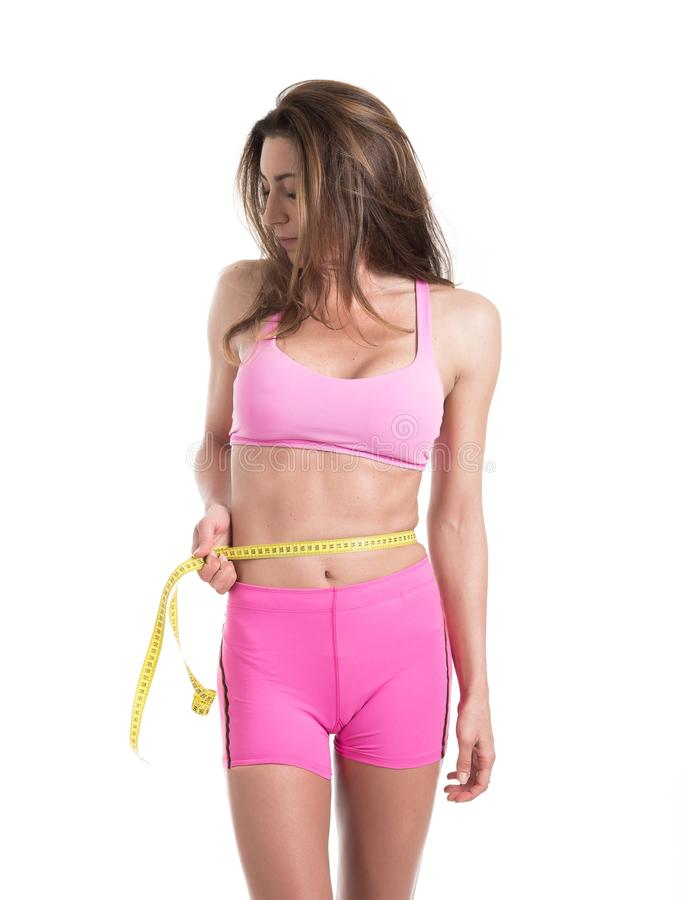 Ciérrese para arriba de las manos femeninas que miden la cintura con la medición de la cinta amarilla Mujer apta y sana en el fon fotografía de archivo