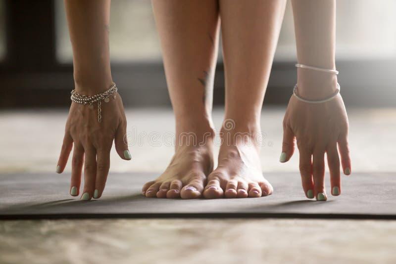 Ciérrese para arriba de las manos femeninas que tocan la estera de la yoga imagenes de archivo