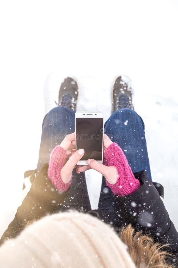 Ciérrese para arriba de las manos de la mujer con los guantes de lana que sostienen smartphone Escena del invierno foto de archivo