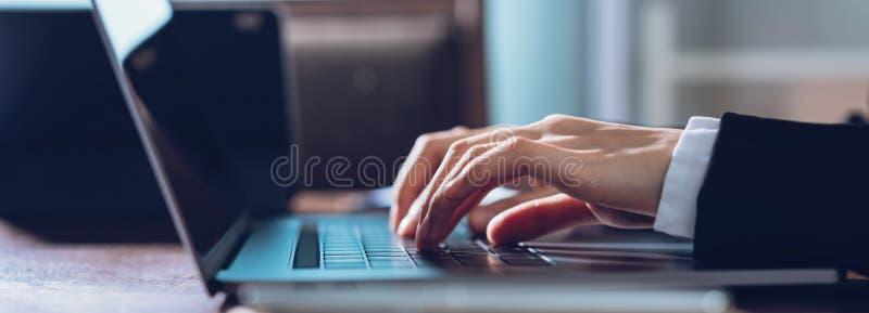 Ciérrese para arriba de las manos de la mujer de negocios que mecanografían en el ordenador portátil y que buscan la web, hojeand foto de archivo libre de regalías