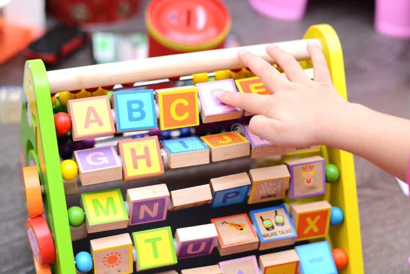 Ciérrese para arriba de las manos de los toddler's que juegan con el juguete educativo fotos de archivo