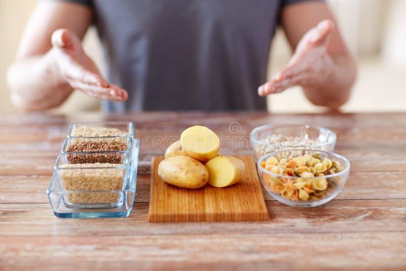 Ciérrese para arriba de las manos masculinas con la comida del carbohidrato foto de archivo libre de regalías