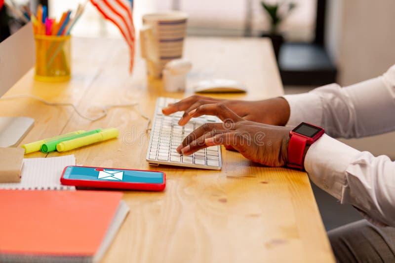 Ciérrese para arriba de las manos masculinas que mecanografían en el teclado fotos de archivo