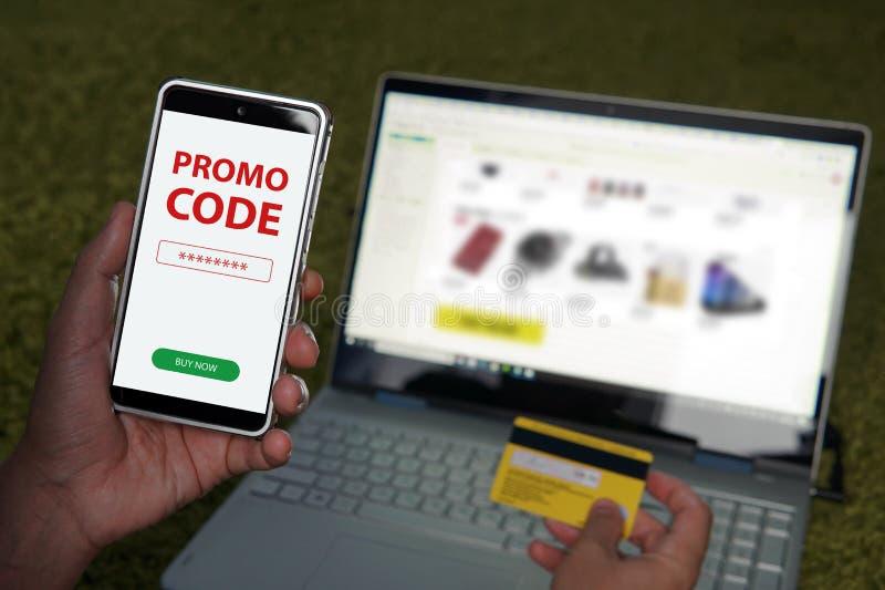 Ciérrese para arriba de las manos masculinas que sostienen smartphone con código rojo del promo de las palabras escritas en la pa imagen de archivo libre de regalías