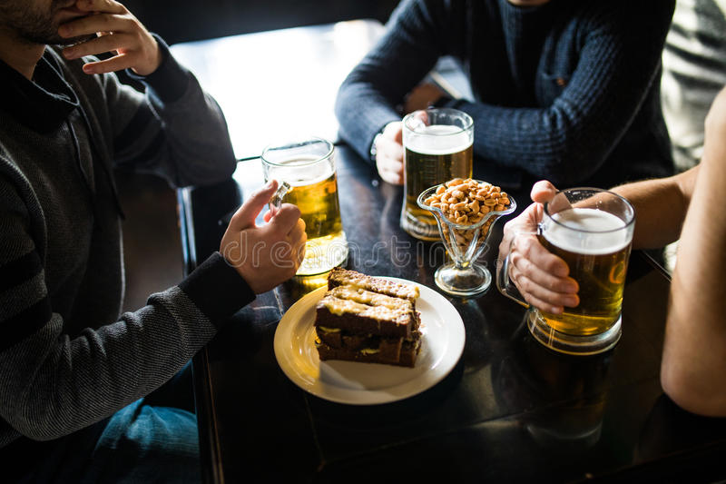 Ciérrese para arriba de las manos masculinas que tintinean los vidrios de cerveza en la barra o el pub imagenes de archivo