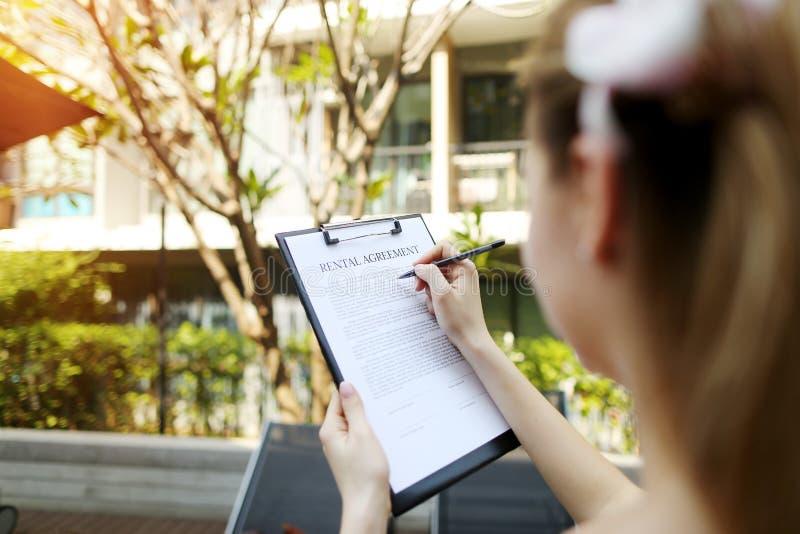 Ciérrese para arriba de las manos que firman el contrato de alquiler del día soleado de la mujer, fondo del apartamento, foco en  imágenes de archivo libres de regalías