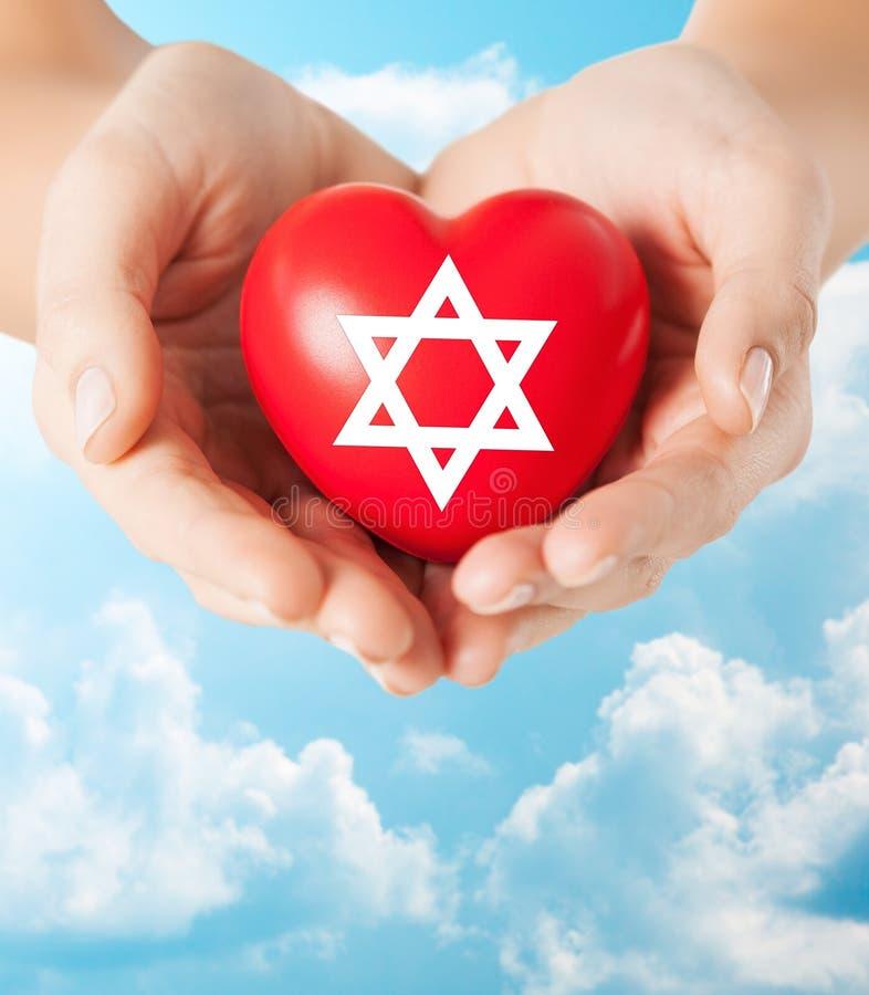 Ciérrese para arriba de las manos que llevan a cabo el corazón con la estrella judía fotos de archivo