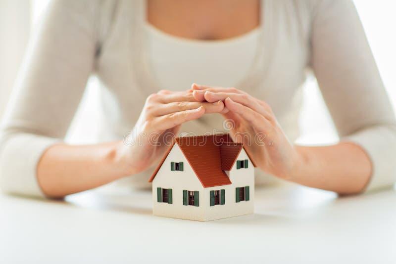 Ciérrese para arriba de las manos que protegen el modelo del casa o casero fotos de archivo