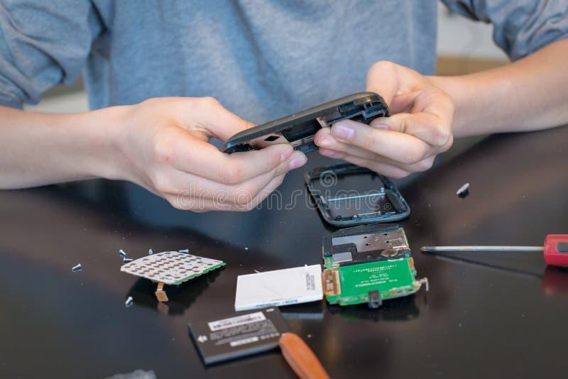 Ciérrese para arriba de las manos que reparan un teléfono móvil fotografía de archivo
