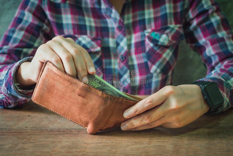 Ciérrese para arriba de las manos que sostienen la cartera de cuero marrón por completo de dinero imagen de archivo