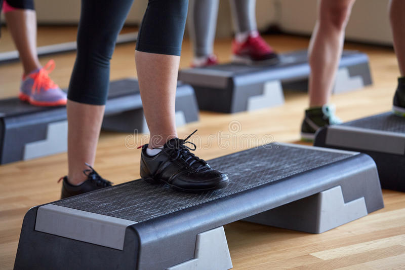 Ciérrese para arriba de las mujeres que ejercitan con los steppers en gimnasio foto de archivo