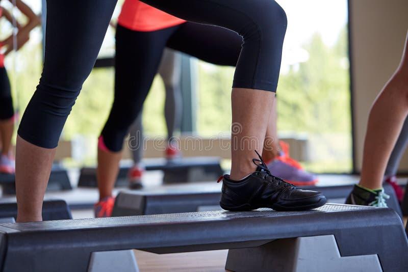 Ciérrese para arriba de las mujeres que ejercitan con los steppers en gimnasio imagen de archivo