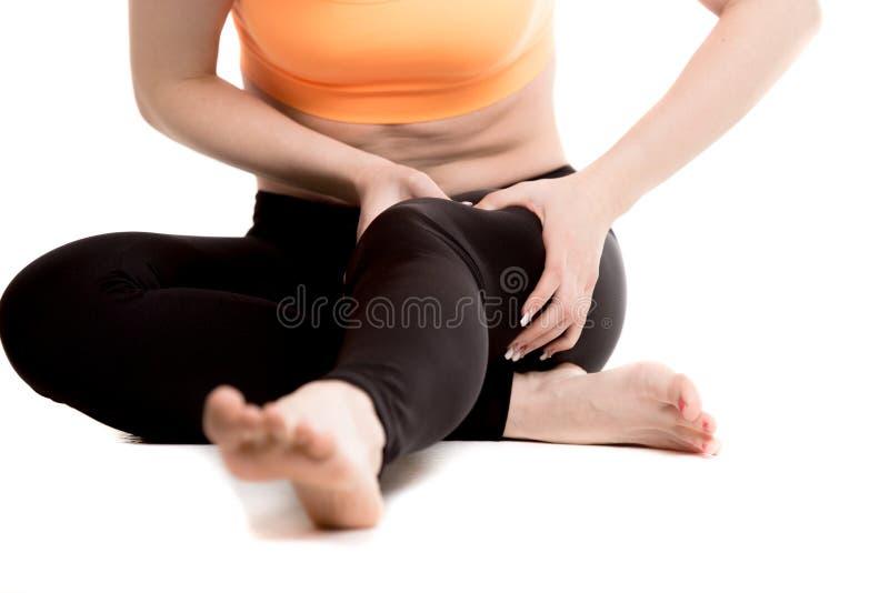 Ciérrese para arriba de las piernas femeninas, muchacha que da masajes al muslo dolorido imagen de archivo