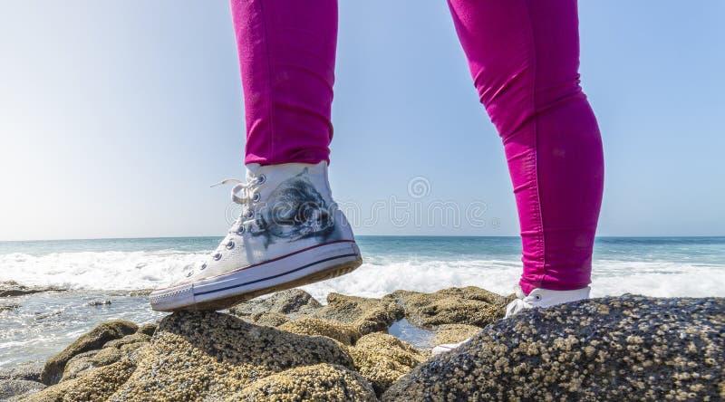 Ciérrese para arriba de las piernas de la mujer que llevan un par de zapatillas de deporte rojas, aislado en blanco foto de archivo
