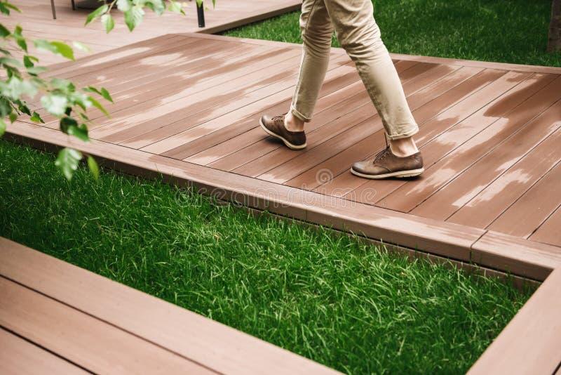 Ciérrese para arriba de las piernas masculinas que caminan en un camino de madera imagen de archivo