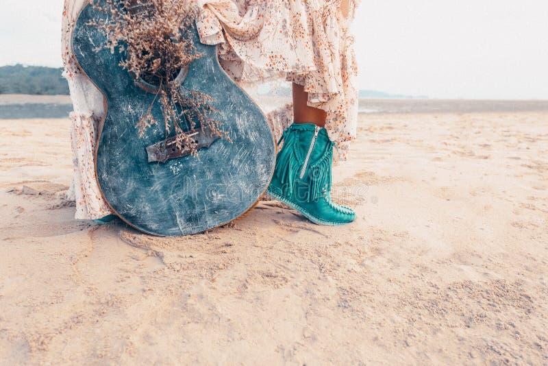 Ciérrese para arriba de las piernas de moda de la mujer joven Modelo de moda con la guitarra al aire libre en la puesta del sol fotos de archivo libres de regalías
