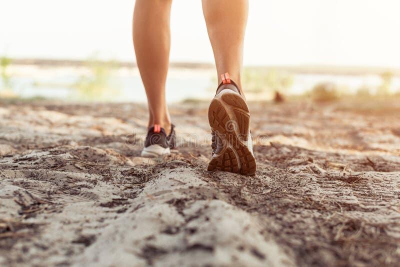 Ciérrese para arriba de las piernas de una mujer joven que se esté fugando el camino en un parque fotografía de archivo libre de regalías