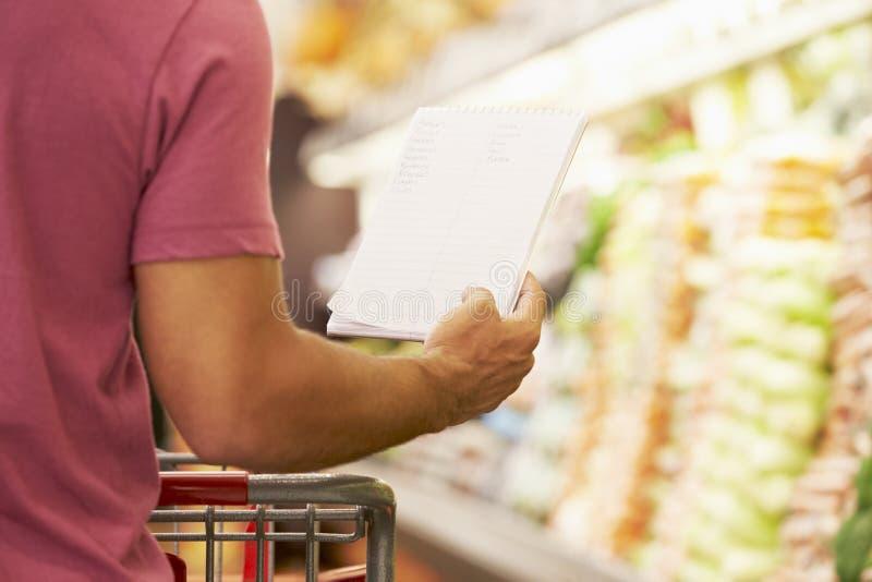 Ciérrese para arriba de lista de compras de la lectura del hombre en supermercado imagen de archivo