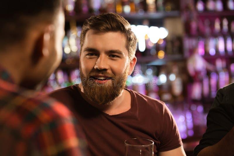 Ciérrese para arriba de los amigos de los dos varones que beben la cerveza de barril imagenes de archivo
