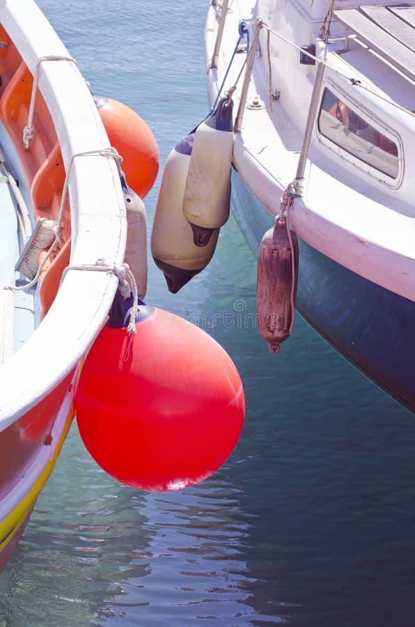 Ciérrese para arriba de los barcos que se colocan además de uno a con las boyas fotos de archivo libres de regalías