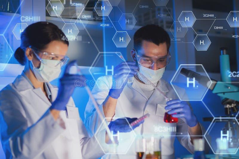 Ciérrese para arriba de los científicos que hacen la prueba en laboratorio imagen de archivo libre de regalías