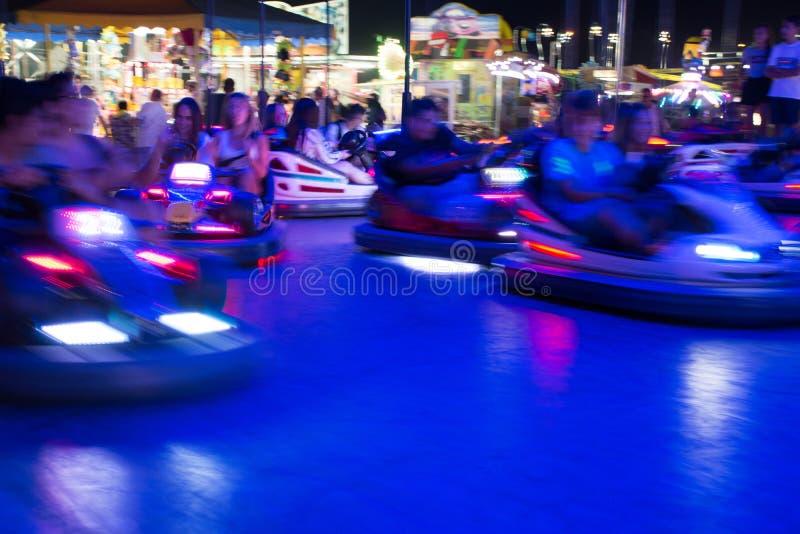 Ciérrese para arriba de los coches de parachoques borrosos que corren en la noche en Luna Park en el sur de Italia imagen de archivo