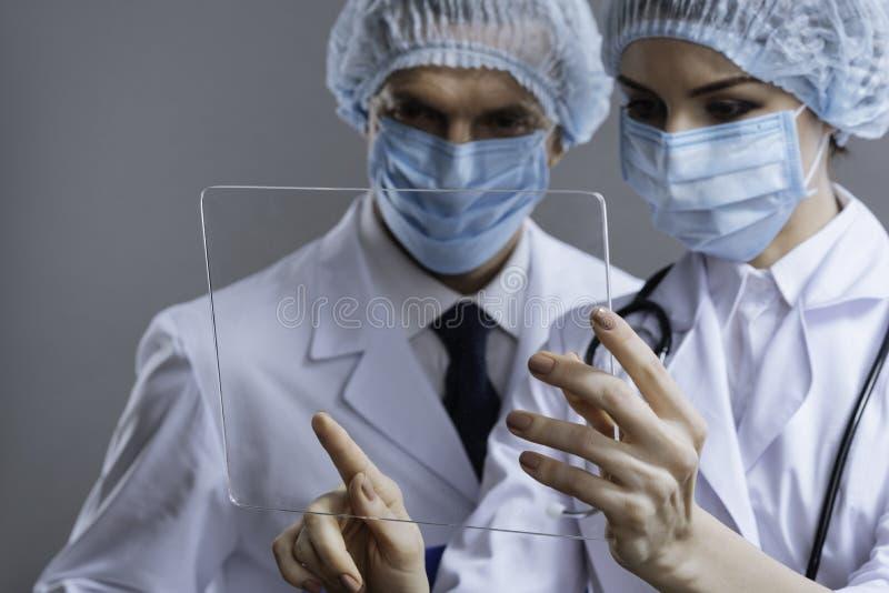 Ciérrese para arriba de los colegas encantados que usan el vidrio médico foto de archivo libre de regalías
