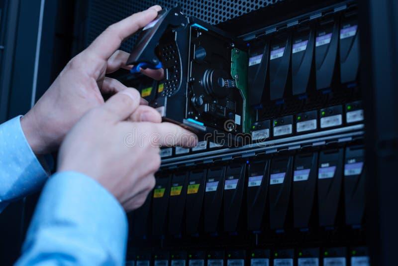 Ciérrese para arriba de los discos duros que se colocan en el estante del servidor foto de archivo