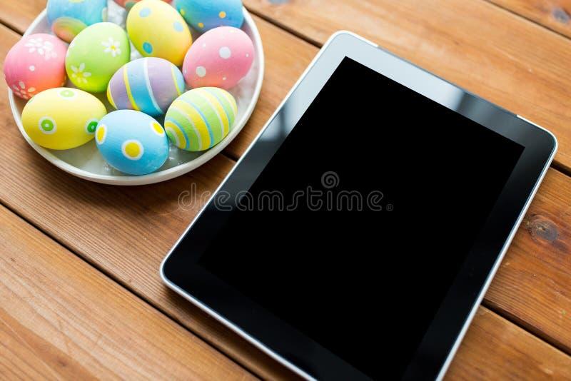 Ciérrese para arriba de los huevos de Pascua y esconda la PC de la tableta foto de archivo