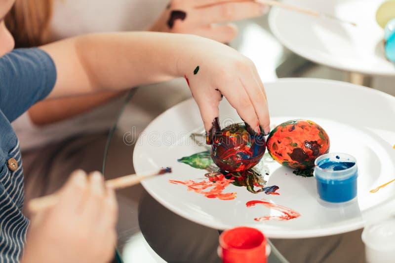 Ciérrese para arriba de los huevos de pintura caucásicos de la mujer y del niño, preparándose para Pascua fotografía de archivo