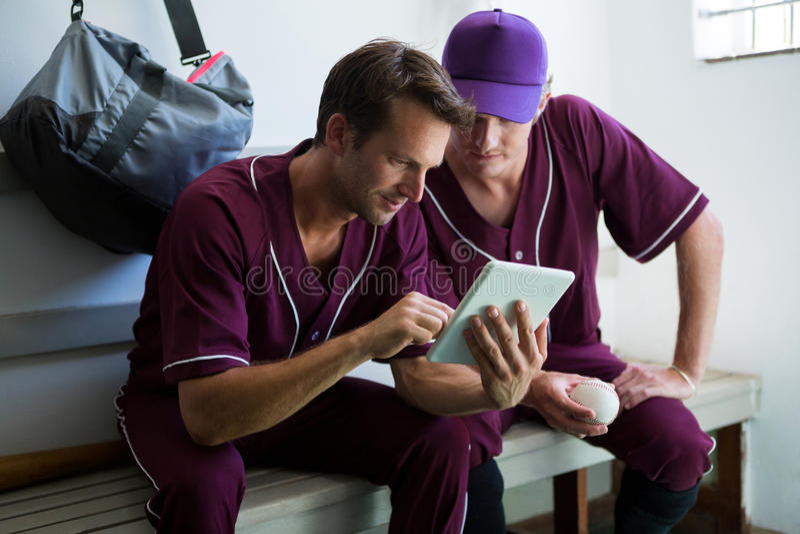 Ciérrese para arriba de los jugadores de béisbol que usan la tableta digital mientras que se sienta en banco fotos de archivo