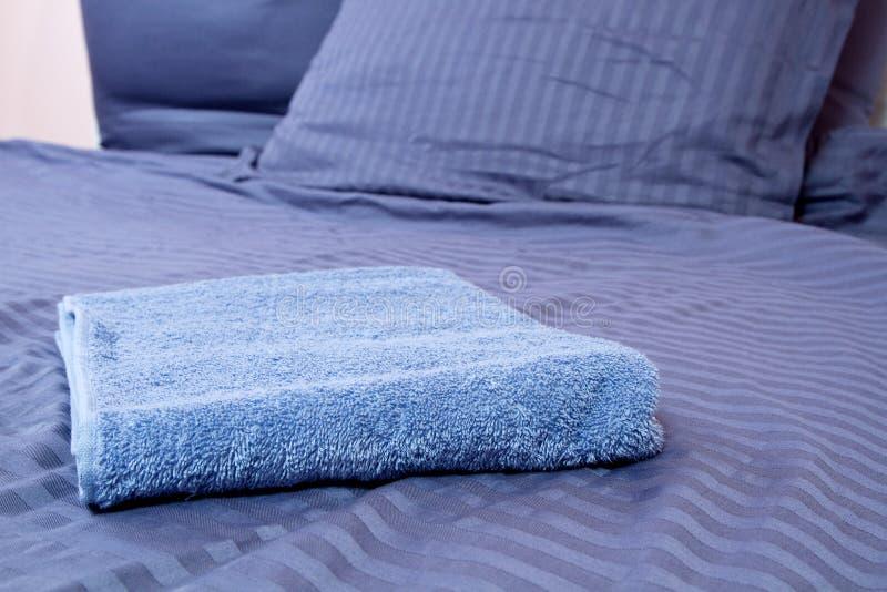Ciérrese para arriba de los linos azules del mesón y de la toalla de baño que mienten en cama Servicio de hotel y fondo limpio de imagen de archivo