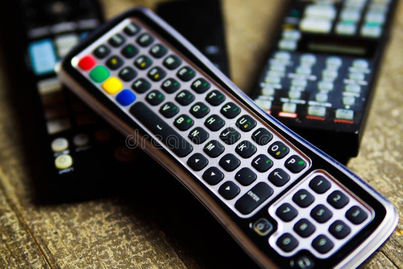 Ciérrese para arriba de los mandos a distancia para la TV, el vídeo y el sistema estéreo de la música en la tabla de madera foto de archivo