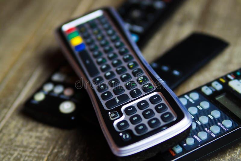 Ciérrese para arriba de los mandos a distancia para la TV, el vídeo y el sistema estéreo de la música en la tabla de madera fotos de archivo