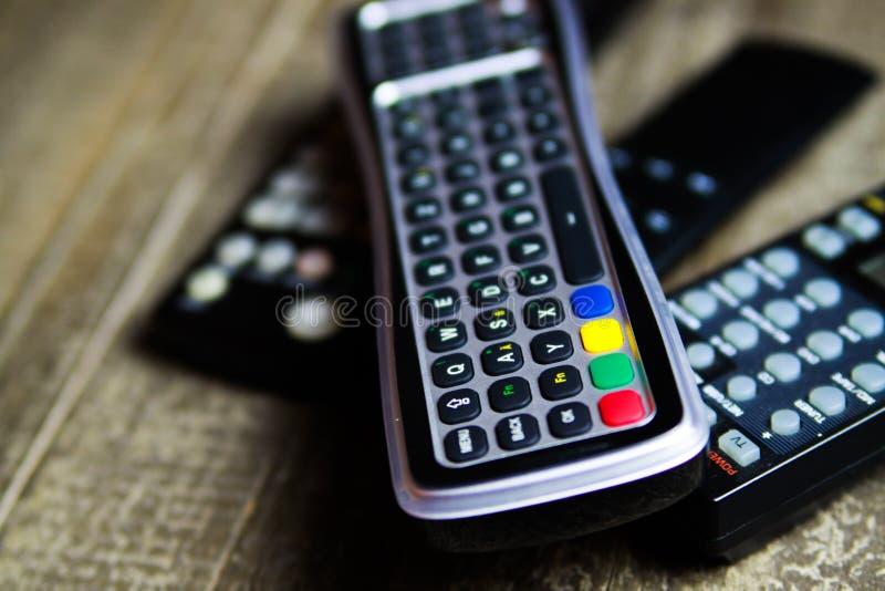 Ciérrese para arriba de los mandos a distancia para la TV, el vídeo y el sistema estéreo de la música en la tabla de madera fotografía de archivo libre de regalías
