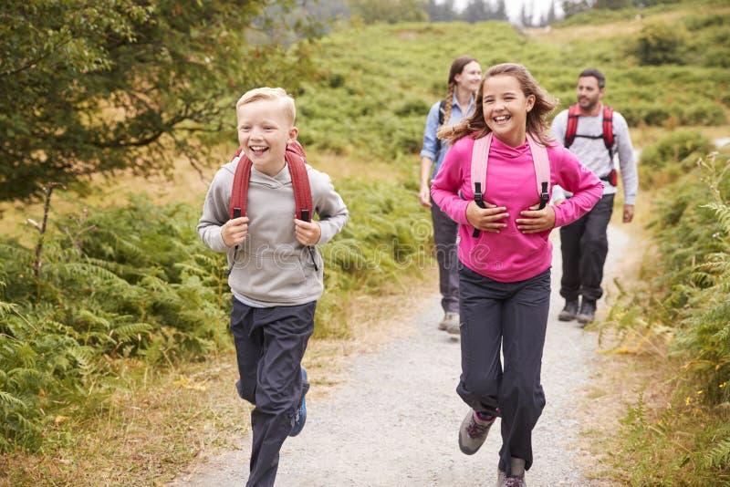 Ciérrese para arriba de los niños que corren delante de padres en una trayectoria del país durante vacaciones de familia, vista d fotografía de archivo