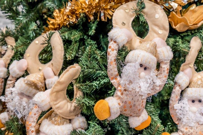 Ciérrese para arriba de los ornamentos decorativos del árbol de navidad de las pequeñas marionetas de oro de Santa Claus fotos de archivo