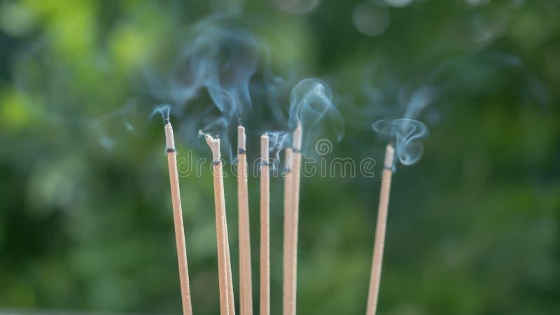Ciérrese para arriba de los palillos ardientes del incienso con humo foto de archivo