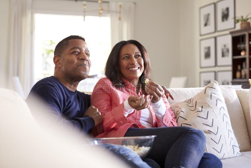 Ciérrese para arriba de los pares envejecidos medios que se sientan en el sofá en su sala de estar que ve la TV, riendo y comiend imágenes de archivo libres de regalías