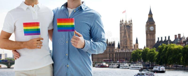 Ciérrese para arriba de los pares gay masculinos con las banderas del arco iris imagenes de archivo