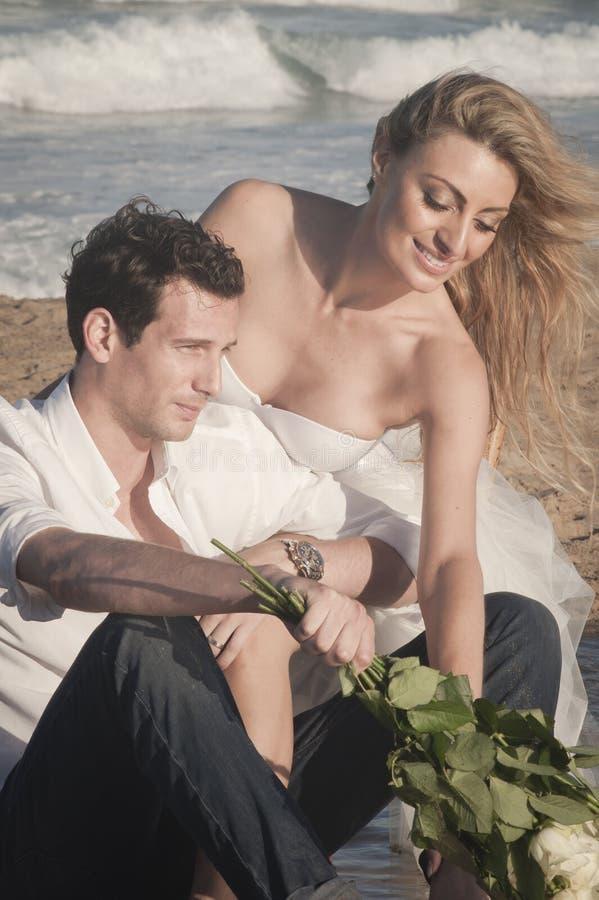 Ciérrese para arriba de los pares hermosos jovenes que se sientan en la playa foto de archivo libre de regalías