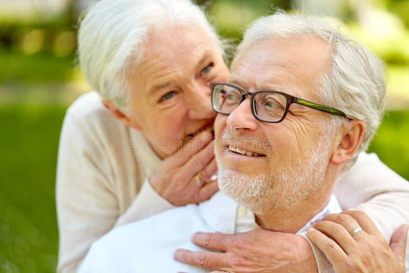 Ciérrese para arriba de los pares mayores que susurran al aire libre fotografía de archivo