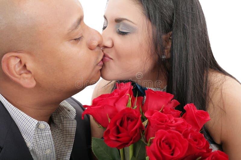 Ciérrese para arriba de los pares que se besan sosteniendo un ramo de rosas rojas imagenes de archivo