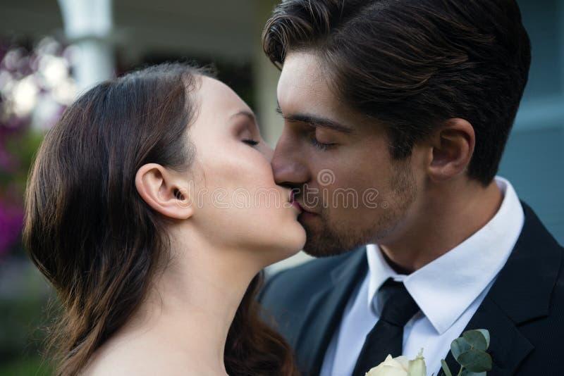 Ciérrese para arriba de los pares románticos del recién casado que se besan en parque foto de archivo