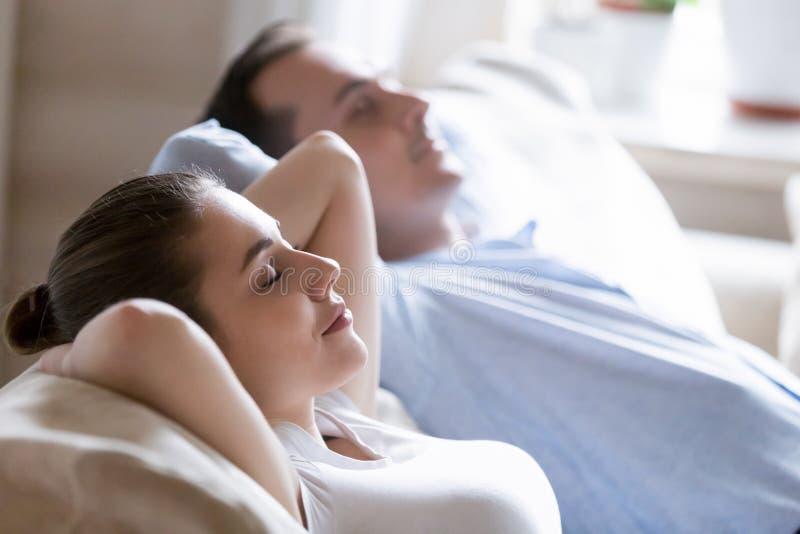Ciérrese para arriba de los pares tranquilos que se relajan en el sofá acogedor imagenes de archivo