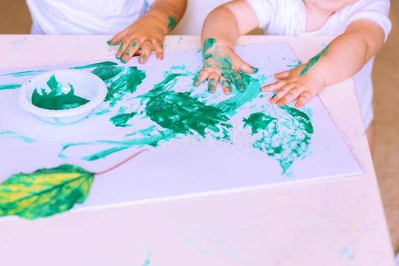Ciérrese para arriba de los pequeños niños de la mano que dibujan con la pintura verde en las hojas de otoño imágenes de archivo libres de regalías