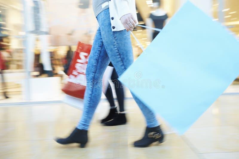 Ciérrese para arriba de los pies de los compradores que llevan bolsos en alameda de compras imagenes de archivo